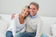 Retrato de un par feliz en sala de estar Imagenes de archivo