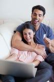 Retrato de un par feliz que reserva sus días de fiesta en línea Imagenes de archivo