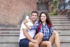 Retrato de un par feliz que toma imágenes de ellos mismos en Fotografía de archivo libre de regalías