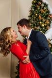 Retrato de un par hermoso en un fondo del árbol de navidad Año Nuevo, vestido rojo, traje de negocios azul Imagenes de archivo