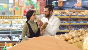 Retrato de un par joven en supermercado, mientras que elige el pan fresco almacen de video