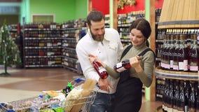 Retrato de un par joven de la moda en una licorería Elegir el vino para la cena almacen de metraje de vídeo