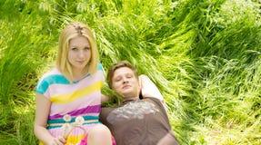 Retrato de un par joven que miente en la hierba Foto de archivo libre de regalías