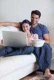 Retrato de un par que mira una película mientras que come las palomitas Foto de archivo