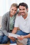 Retrato de un par sonriente que lee una letra Imagen de archivo