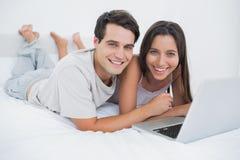 Retrato de un par usando un ordenador portátil que miente en cama Fotografía de archivo libre de regalías