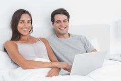 Retrato de un par usando un ordenador portátil junto que miente en cama Imagen de archivo libre de regalías