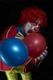Retrato de un payaso triste que sostiene dos globos Foto de archivo libre de regalías