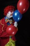 Retrato de un payaso triste que sostiene tres globos Foto de archivo libre de regalías