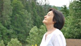 Retrato de un pensionista relajado feliz de vacaciones en las montañas Aire fresco de la montaña, concepto del viaje, el día de m almacen de metraje de vídeo