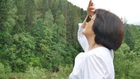 Retrato de un pensionista relajado feliz de vacaciones en las montañas La mujer saca las gafas de sol y mira en almacen de metraje de vídeo
