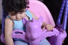 Retrato de un pequeño bebé soñoliento en el oscilación del unicornio fotografía de archivo