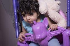 Retrato de un pequeño bebé soñoliento en el oscilación del unicornio con el tedd fotografía de archivo