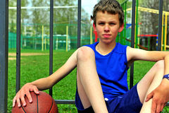 Retrato de un pequeño jugador de básquet que se sienta en la corte Imagen de archivo libre de regalías