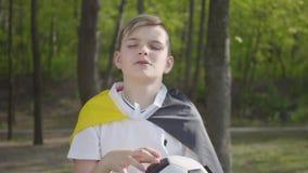 Retrato de un pequeño muchacho adorable que lanza para arriba un balón de fútbol Reconstrucci?n al aire libre almacen de video