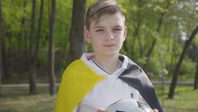 Retrato de un pequeño muchacho adorable que sostiene un balón de fútbol Reconstrucci?n al aire libre almacen de metraje de vídeo