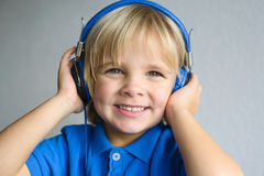 Retrato de un pequeño muchacho sonriente con el auricular Foto de archivo libre de regalías