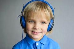Retrato de un pequeño muchacho sonriente con el auricular Fotos de archivo libres de regalías