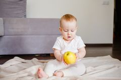 Retrato de un pequeño niño lindo con una manzana amarilla, sentándose en el piso Bebé de 9 meses del bebé que sostiene una fruta imágenes de archivo libres de regalías