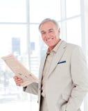 Retrato de un periódico sonriente de la lectura del encargado Foto de archivo libre de regalías