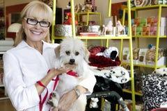 Retrato de un perro que lleva de la mujer mayor feliz en la tienda de animales Imagenes de archivo