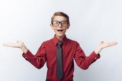 Retrato de un positivo y adolescente sorprendido en un fondo blanco, con los vidrios, camisa roja, publicidad, inserción del text Fotografía de archivo libre de regalías