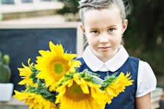 Retrato de un primero-graduador joven hermoso con con el ramo de girasoles en un uniforme escolar festivo Imagenes de archivo