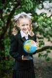 Retrato de un primero-graduador joven hermoso con el globo con el texto ruso en un uniforme escolar festivo Foto de archivo