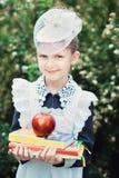 Retrato de un primero-graduador joven hermoso con la manzana roja en los libros en un uniforme escolar festivo Imagenes de archivo