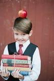 Retrato de un primero-graduador que se coloca con los libros y la manzana en la cabeza Imagen de archivo