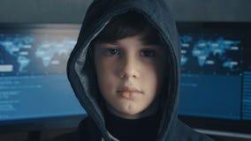 Retrato de un prodigio del pirata informático del muchacho del genio en la capilla en el fondo de monitores con código de program almacen de metraje de vídeo