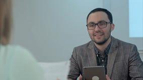 Retrato de un profesor sonriente con la tableta en el cuarto de clase Imagenes de archivo