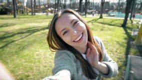 Retrato de un selfie hermoso de la mujer joven en el parque con un teléfono elegante almacen de metraje de vídeo