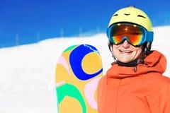 Retrato de un snowboarder que sonríe en el top de las montañas Imagen de archivo