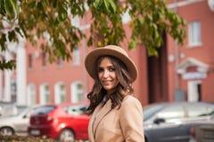 Retrato de un sombrero y de una capa que llevan de la muchacha contra las máquinas urbanas del paisaje del contexto Fotos de archivo