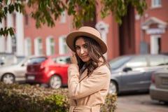 Retrato de un sombrero y de una capa que llevan de la muchacha contra las máquinas urbanas del paisaje del contexto fotografía de archivo