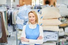 Retrato de un trabajador de la muchacha en un lavadero del almacén con ropa limpia imagenes de archivo