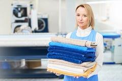 Retrato de un trabajador del lavadero de la muchacha que sostiene una toalla limpia imagen de archivo libre de regalías