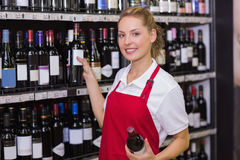 Retrato de un trabajador rubio sonriente que toma una botella de vino Fotografía de archivo