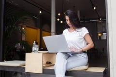 Retrato de un trabajo femenino del freelancer joven en su red-libro mientras que se sienta en cafetería moderna en día de verano Imagenes de archivo