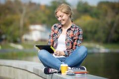 Retrato de un turco que se sienta del estudiante en el puente con la tableta Fotografía de archivo