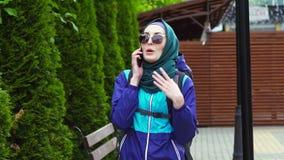 Retrato de un turista de la muchacha en un pañuelo y de gafas de sol con una mochila que hablan en el teléfono almacen de metraje de vídeo