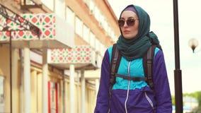 Retrato de un turista de la muchacha en un pañuelo y de gafas de sol en una mochila almacen de video