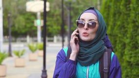 Retrato de un turista de la muchacha en un pañuelo y de gafas de sol en una mochila que hablan en el teléfono almacen de video