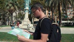 Retrato de un turista que mira el mapa en camino almacen de metraje de vídeo
