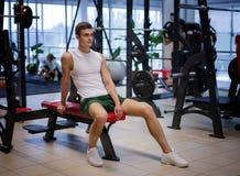 Retrato de un varón deportivo con un cuerpo muscular en un fondo del gimnasio Un culturista con un cuerpo perfecto en un club de  Fotos de archivo libres de regalías