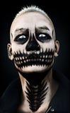 Retrato de un varón que mira fijamente feroz asustadizo con maquillaje y perforaciones del cráneo en un fondo negro representació Imagen de archivo libre de regalías