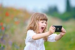 Retrato de un vestido blanco que lleva de la muchacha feliz mientras que mira el stre Imagen de archivo