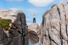 Retrato de un viaje extremo del plan para el viejo hombre hermoso en la piedra del kjerag en las montañas de Noruega, s imagen de archivo