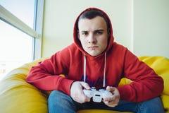 Retrato de un videojugador joven con una palanca de mando en sus manos que juegan a un videojuego en la consola Videojuegos del c Imagenes de archivo